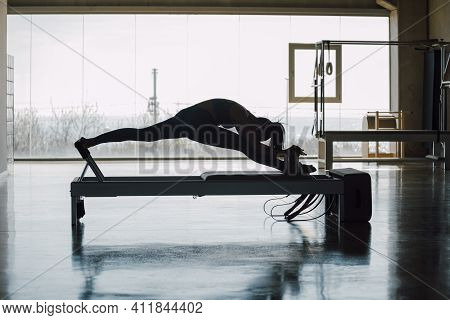 Fit Female Instructor Practicing Pilates Exercises Routine On A Reformer Bed Machine, Slim Woman Wor