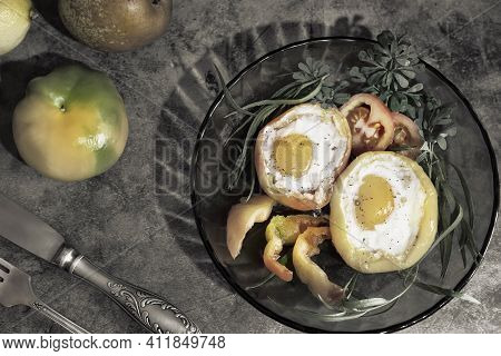 On The Table On Plates Are Baked In The Oven Bell Peppers With An Egg Inside Each Pepper. There Are