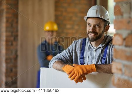 Portrait Of Positive, Handsome Young Male Builder In Hard Hat Smiling At Camera, Holding Drywall Whi