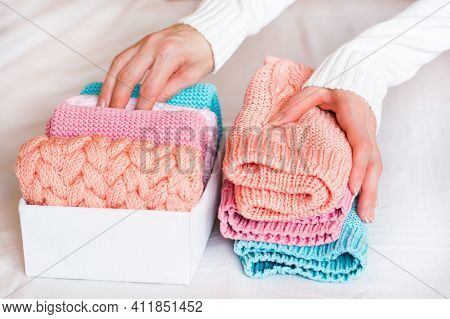 Organization And Order. Female Hands Fold Knitted Clothes In A Pile Next To A Box With Neatly Folded