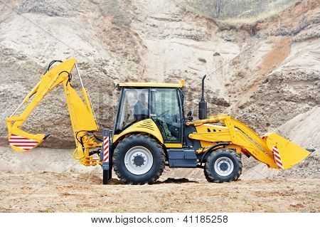 Wheel loader Excavator with backhoe loading sand at eathmoving works in construction site