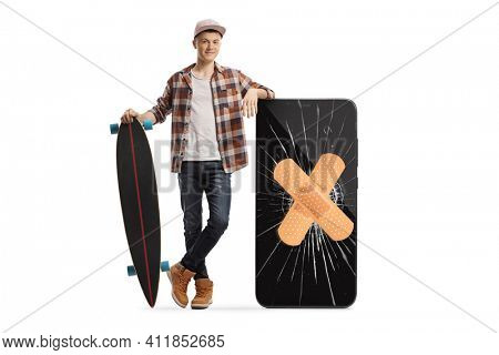 Full length portrait of a skater guy with a longboard posing next to a phone with a cracked screen and bandage isolated on white background