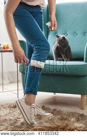 Woman Cleaning Clothes With Sticky Roller From Cats Hair.cleanin