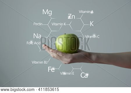 Woman`s Hand Holding Green Apple, Microelement Icons In Molecular Hexagons On Grey Background. Healt