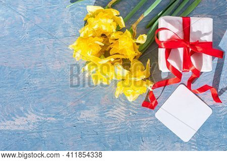 Yellow Bright Daffodils, White Gift Box With Red Ribbon And Blank White Card On Blue Wooden Backgrou