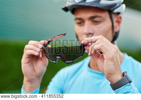 Portrait Of Professional Young Male Cyclist Wearing Suit Holding, Putting On Protective Glasses Whil