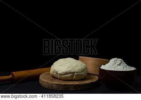 Dough On A Dark Background. A Piece Of Homemade Dough On A Wooden Board On A Black Background. The T