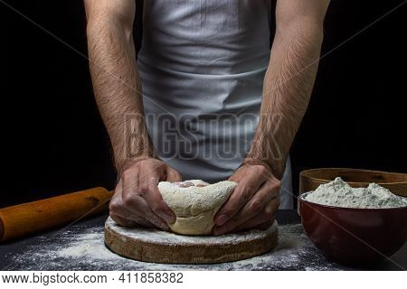 Dough On A Dark Background. Male Hands Knead The Dough. Chef Working With Dough On Black Background