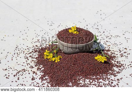 Organic Black Mustard Seed In Stone Bowl With Yellow Mustard Flower Isolated White Background