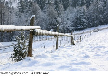 wooden fence on border of snovy meadow