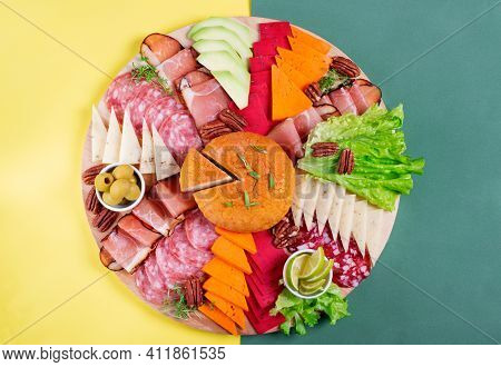 Cheese And Sausage Board. Assortment Of Served Appetizers On Geometric Yellow And Green. Top View