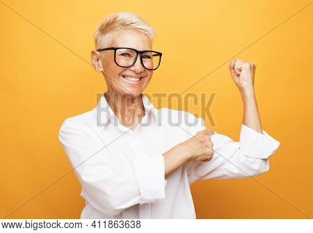 Lifestyle and old people concept: Senior grey-haired woman showing arm muscle