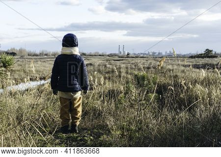 Back View Of A Child Wearing Winter Clothes Standing In Front Of Wild Landscape And Factories On Bac