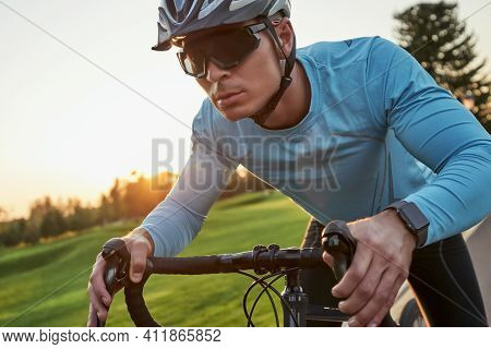 Get Faster. Serious Young Male Racer In Sportswear And Protective Helmet Looking Focused While Ridin