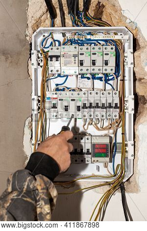 Anapa, Russia-07.11.2020: Electrical Switchboard. A Male Electrician Installs A Multifunctional Shie