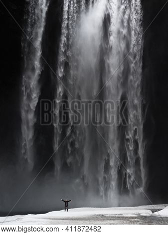 Woman with Raised Up Hands Admires the Splendor of the Huge Waterfall. Amazing Beauty of Skogafoss Waterfall. Iceland.