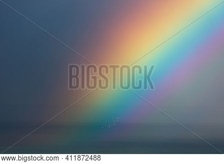Beautiful Landscape of an Amazing Rainbow over Sea. Multicolored Phenomenon in the Sky. Beauty of Nature. Gorgeous Natural Background.