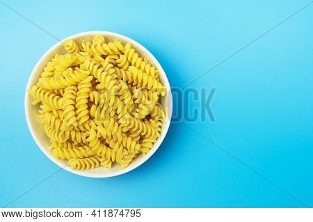 Fusilli Italian Pasta In White Ceramical Bowl On Blue Background With Space For Text, Top View.