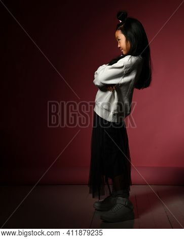 Fashion Portrait Of A Korean Girl Poses For The Camera In A Dark Room On A Red Wall. The Girl Is Wea