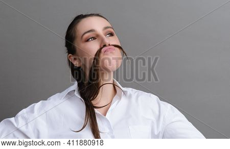 1 White Funny Young Woman 20 Years Old In A White Shirt Fooling Around, Holding Her Hair Near Her Fa