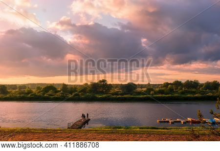 A Small River With A Wooden Pier Is Illuminated By The Setting Sun. The Sky Is Dark And Stormy.