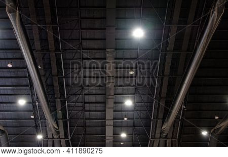 The Truss Metal Frame With The Electric Bulb System On The Ceiling Of The Modern Warehouse, Used For