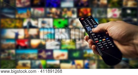 Tv Channels In Background And Remote Control In Hand. Smart Television And Content On Demand Concept