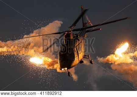 Military Helicopter Firing Flare Decoys During A Evening Flight.