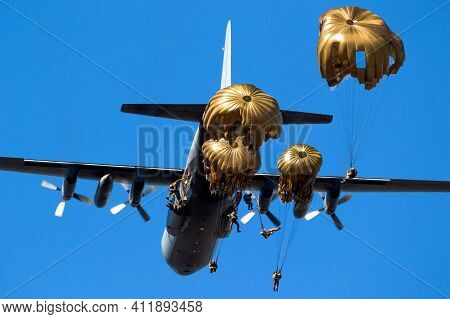 Group Of Military Parachutist Paratroopers Jumping Out Of A Military Transport Plane.