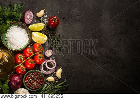 Food Background On Black Slate Table. Ingredients For Cooking Food - Tomatoes, Onion, And Herbs. Top