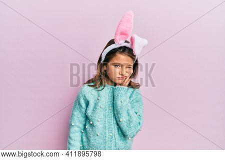 Little beautiful girl wearing cute easter bunny ears touching mouth with hand with painful expression because of toothache or dental illness on teeth. dentist