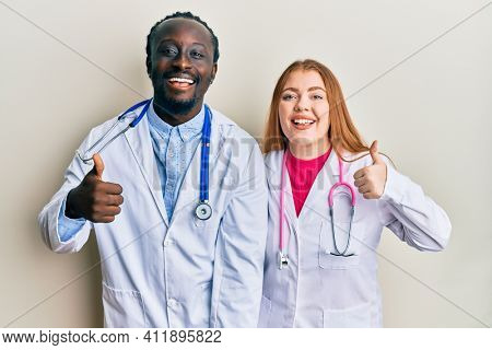 Young interracial couple wearing doctor uniform and stethoscope success sign doing positive gesture with hand, thumbs up smiling and happy. cheerful expression and winner gesture.