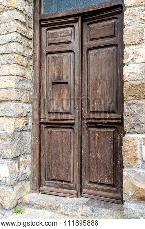 Architectural Detail Of A Massive Brown Wooden Door In A Massive Brown Stone Building