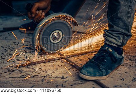 Steel Cutter Saw at Work. Closeup Photo of a Hot Bright Sparks Fly Out from under the Welding, Hard Work, Blue Collar Worker.