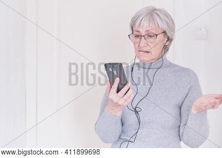 A Gray-haired Senior Woman With Glasses And A Gray Turtleneck Using Mobile Phone At Home Thoughtfull