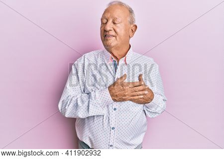 Senior caucasian man wearing casual clothes smiling with hands on chest, eyes closed with grateful gesture on face. health concept.