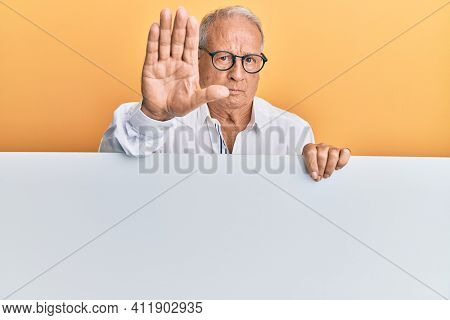 Senior caucasian man holding blank empty banner with open hand doing stop sign with serious and confident expression, defense gesture