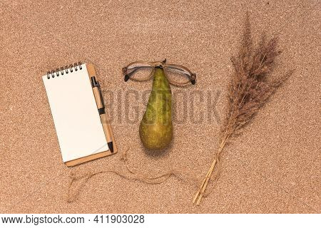 Top View Of Blank Empty Notepad, Glasses On Pear And Dry Grass On Cork Table. Funny Anthropomorphic