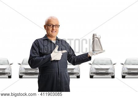 Auto mechanic holding an engine oil in a car showroom isolated on white background