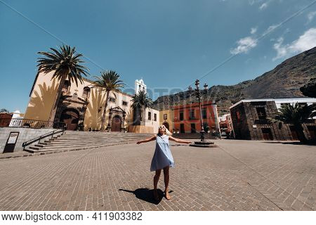 A Girl In A Blue Dress Walks Through The Old Town Of Garachico On The Island Of Tenerife On A Sunny