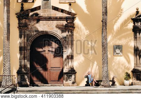 A Girl In A Blue Dress Sits On A Bench In The Old Town Of Garachico On The Island Of Tenerife On A S