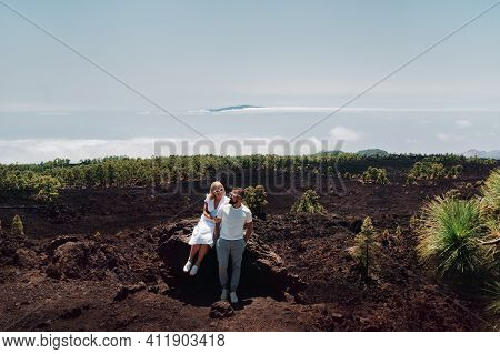 The Family In White Clothes Are Tourists Traveling Through The Summer Mountains Of The Teide Volcano