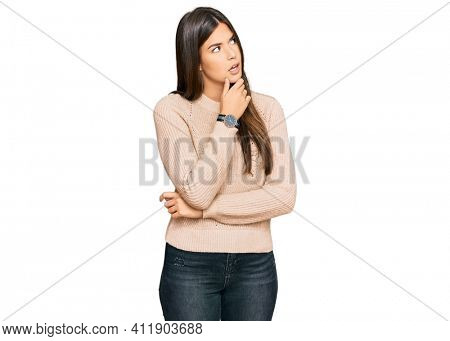 Young brunette woman wearing casual winter sweater thinking worried about a question, concerned and nervous with hand on chin