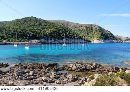 The Coast Of The Bay Of The Island Of Mallorca With Blue Water And A Stone Coast, In The Bay There A