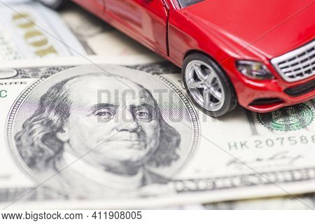 Red Toy Car On Dollar Bills. Cost Of Buying A Car, Fuel, Insurance And Other Car Costs. Rent, Buy Or