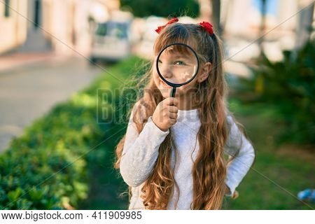 Adorable caucasian child girl  smiling happy using loupe at the city.