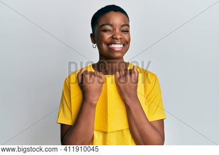 Young african american woman holding book winking looking at the camera with sexy expression, cheerful and happy face.