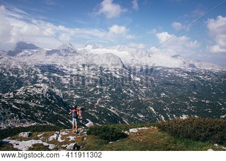 Dark-skinned Man With A Backpack On His Back Looks At The Dachstein Massif In Upper Austria. A Purpo