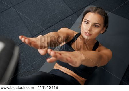 Close Up Of Beautiful Young Brunette Doing Abs On Black Mat In Modern Gym. Concept Of Workout And Pu