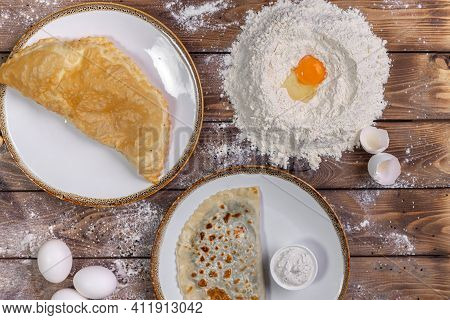 Chebureks On A Plate, Sauce, Flour, Chicken Eggs On A Brown Wooden Background. Flat Layout.